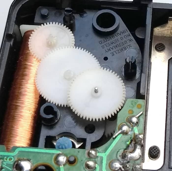 Dentro del reloj, un electroimán mueve el pequeño rotor magnético azul media vuelta cada segundo.  Esto hace girar los otros engranajes.